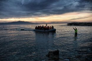 (FILES) This file photo taken on February 17, 2016 shows Refugees and migrants massed onto an inflatable boat reaching Mytilene, northern island of Lesbos, after crossing the Aegean sea from Turkey. The Greek tourist island of Lesbos was once known to Greeks mainly for its potent ouzo, and to the rest of world as the homeland of Sappho, the seventh century poet who immortalised love for women. But in its new role as the main gateway into Europe for hundreds of thousands of refugees and migrants since last year, Lesbos has also become a base for dozens of aid groups and an obligatory destination for European leaders, prominent artists and now Pope Francis, who is visiting on April 16, 2016. / AFP PHOTO / ARIS MESSINIS